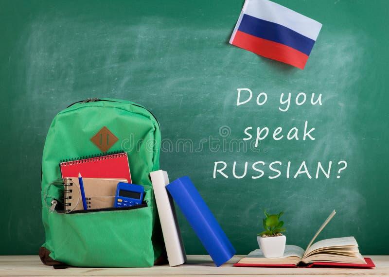 рюкзак, классн классный с текстом & x22; Вы говорите по-русски? & x22; , флаг России, калькулятор, книги и тетради стоковые фотографии rf