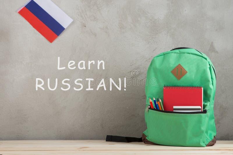 рюкзак, флаг России, ведомство канцлера и тетради против стены цемента с текстом ' Выучите русск стоковое фото rf