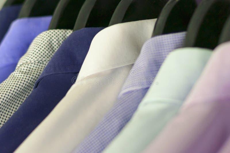 Рубашки нескольких людей других цветов на вешалках Селективный фокус стоковое изображение rf