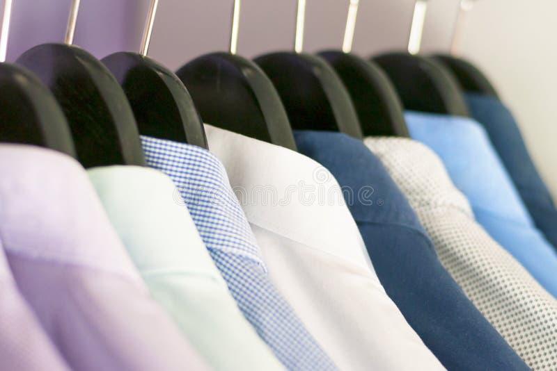Рубашки нескольких людей других цветов на вешалках Селективный фокус стоковая фотография