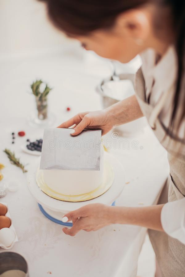 Рука женщины держа pstry резец пока подготавливающ торт стоковое изображение rf