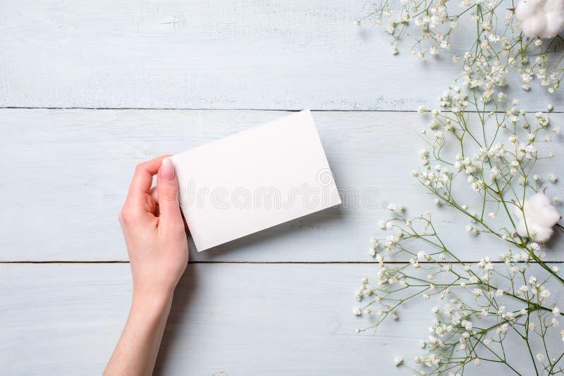 Рука женщин держа карту чистого листа бумаги на светлом - голубая деревянная предпосылка Деревенская таблица с цветками, карта пр стоковое фото