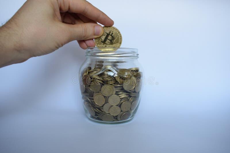 Рука кладет монетку bitcoin в опарник монеток стоковое изображение rf