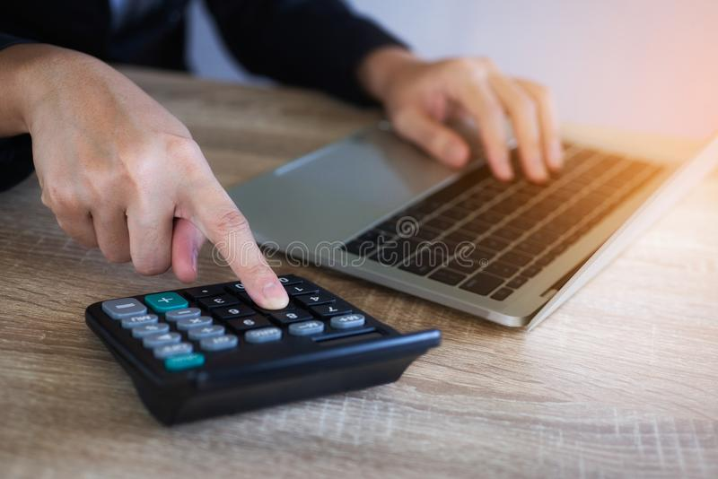 Рука крупного плана бизнес-леди работая с калькулятором и ноутбук для анализируют отчет на офисе стоковые фото