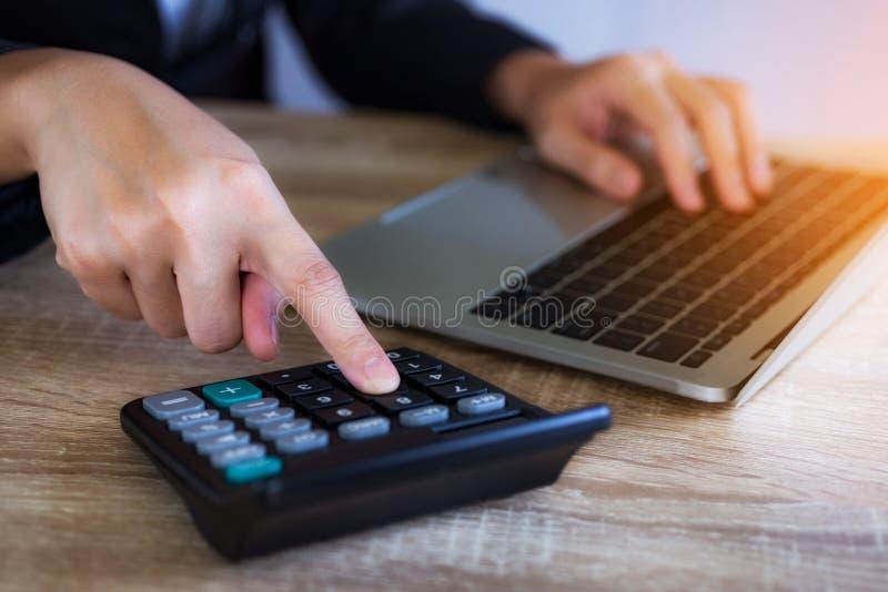Рука крупного плана бизнес-леди работая с калькулятором и ноутбук для анализируют отчет на офисе стоковые изображения
