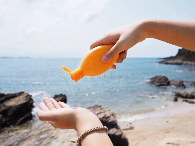 Рука держа бутылку сливк sunblock и лить над предпосылкой пляжа лета стоковое изображение rf