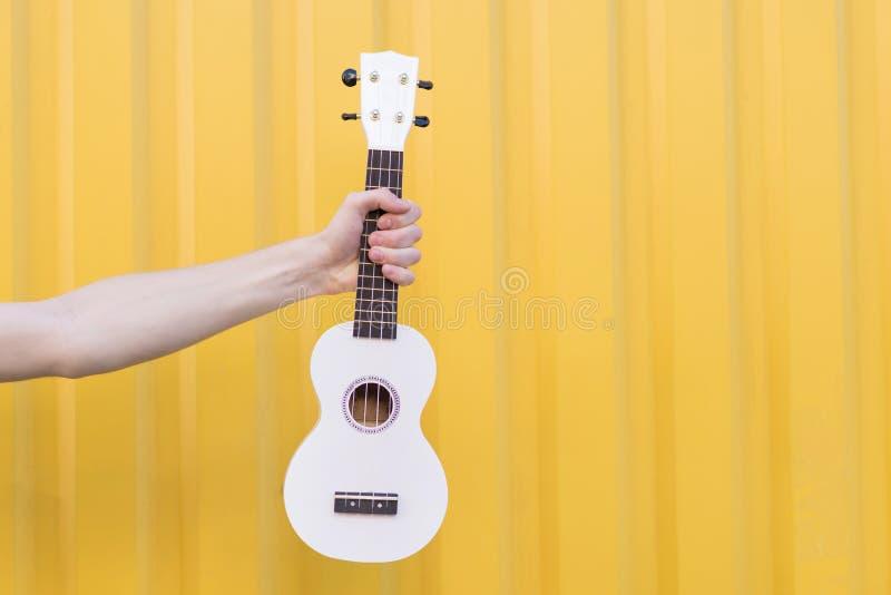 рука держа гавайскую гитару на желтой предпосылке Музыкальная принципиальная схема стоковые фото