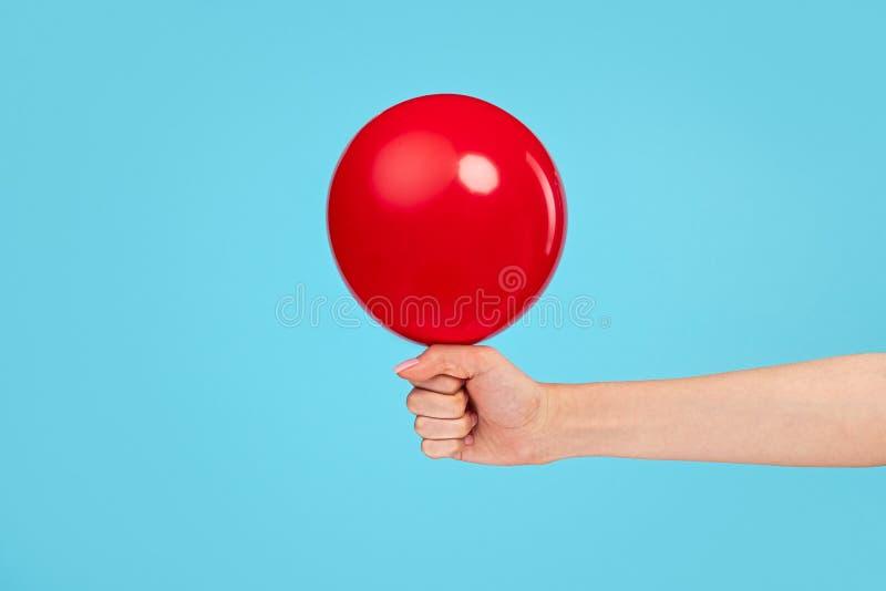 Рука держа красный воздушный шар на голубом фоне стоковая фотография