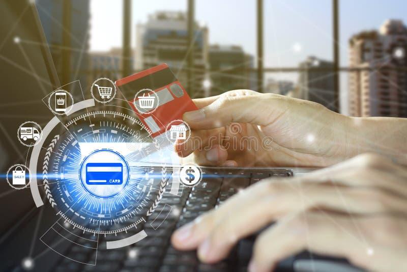 Рука держа кредитную карточку и используя ноутбук с онлайн ходя по магазинам технологией значков, онлайн ходя по магазинам концеп стоковая фотография