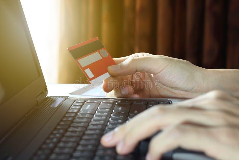 Рука держа кредитную карточку и используя ноутбук, онлайн ходя по магазинам концепцию стоковое изображение