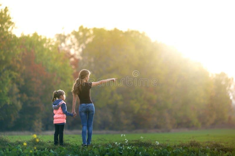 Рука удерживания девушки маленького ребенка привлекательной матери в зеленом outdoors луга наслаждаясь природой на предпосылке за стоковые изображения