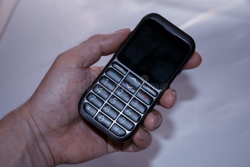 Рука человека держит старый кнопочный телефон стоковые фотографии rf