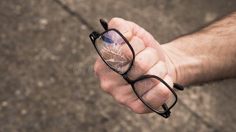 рука человека обхватила в кулак со сломленными стеклами стоковое фото rf