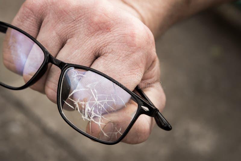 рука человека обхватила в кулак со сломленными стеклами стоковое изображение rf