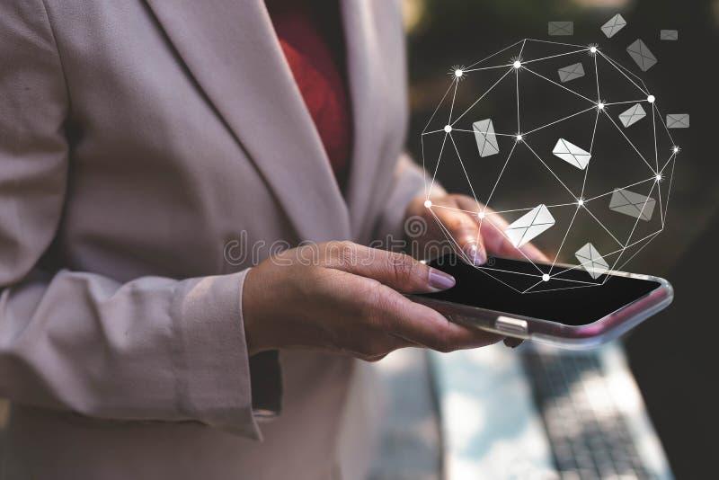 Руки бизнес-леди используя мобильный телефон читая, отправляя и соединяясь со значком электронной почты Бизнесмены независимые, н стоковые изображения