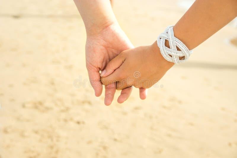 Руки владением человека и женщины молодых пар кавказские Предпосылка взморья песка пляжа солнечного света лета яркая Семейное отн стоковое изображение rf