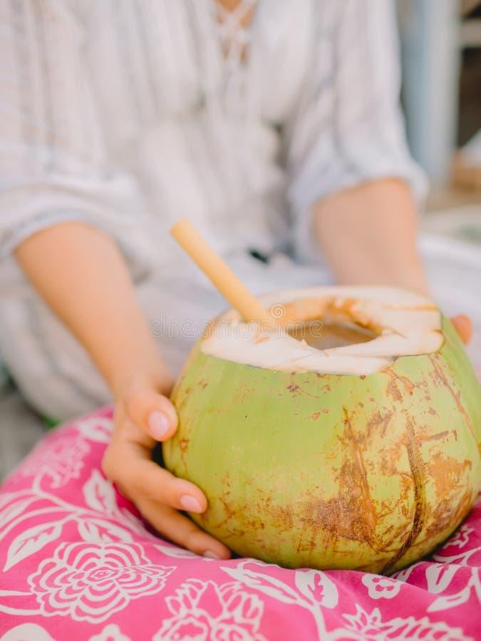 Руки женщины и свежий кокос с бамбуковой соломой стоковая фотография