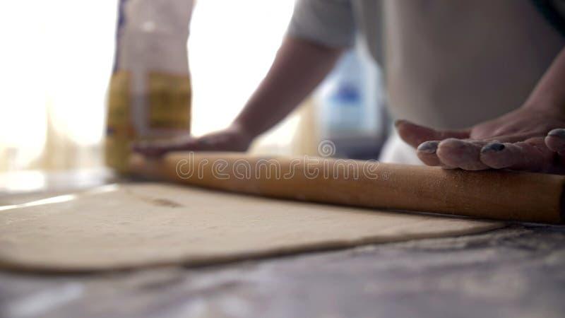 Руки женщины делая тесто для хлеба или пиццы, используя вращающую ось, печь стоковое изображение rf