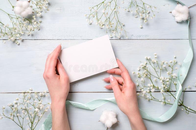 Руки держа карту чистого листа бумаги на светлом - голубой деревянный стол с цветками Нежная поздравительная открытка на день жен стоковое фото rf