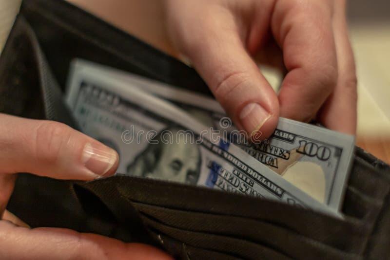 Руки держа счеты доллара США и небольшой мешок денег стоковое фото