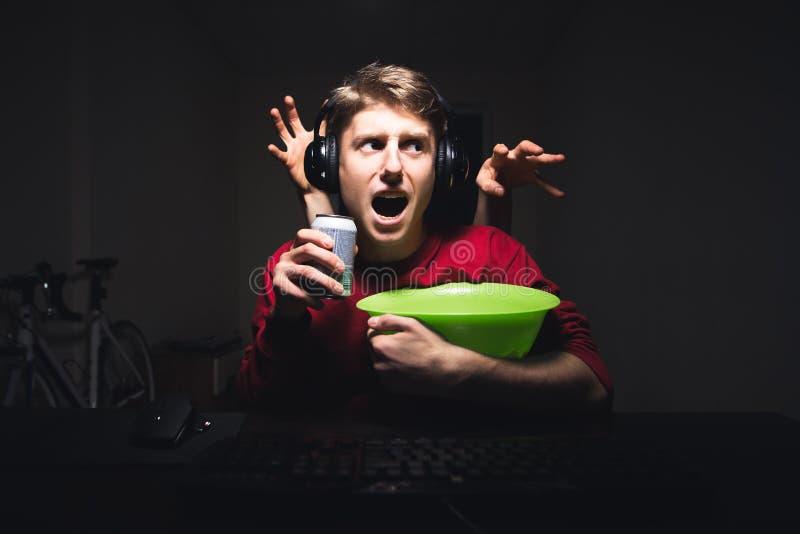 Руки от задней части хотят хватать молодого человека сидя вечером в комнате с закуской и напитке в его руках стоковое фото