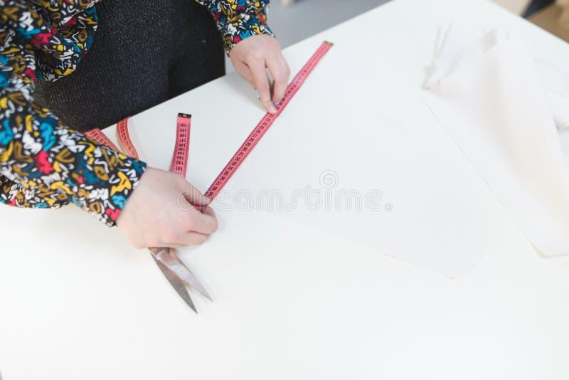 Рулетка длины белошвейки руки на белой предпосылке предпосылка застегивает резьбу 2 темной иглы принципиальной схемы крупного пла стоковое изображение rf