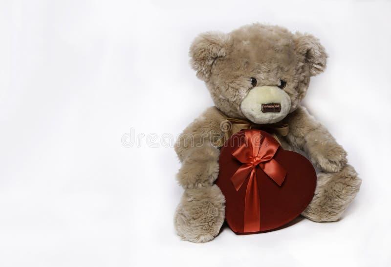 Русая плюшевый мишка держа сердце любов стоковая фотография rf