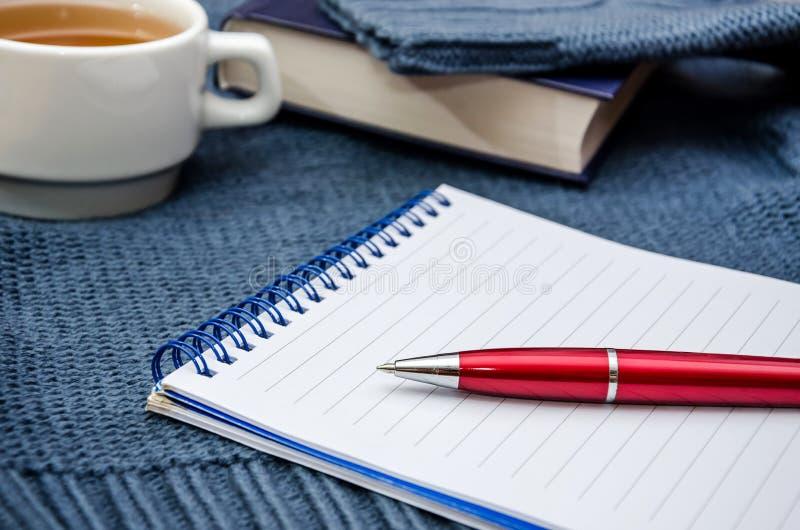 Ручка и блокнот на голубой предпосылке Книга и чашка чаю на заднем плане стоковая фотография rf