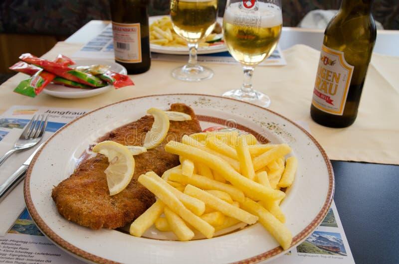 Рыбы и обломоки и пиво служили на кафе в Grindelwald Швейцария стоковые фото