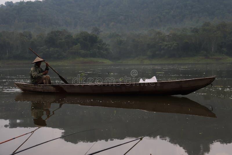 Рыболов, деревянная шлюпка, пресноводное озеро стоковое изображение