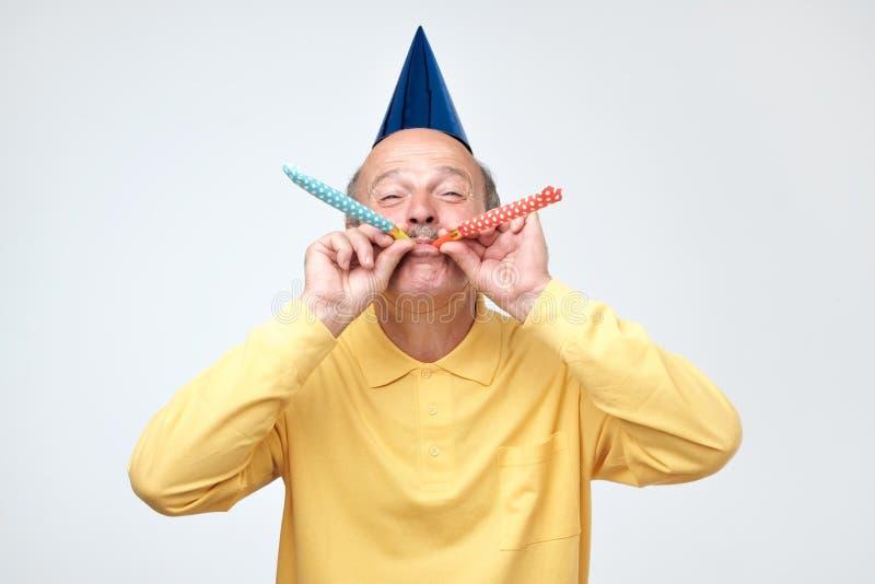 Рожок партии старшего человека дуя возбуждая взгляд пока празднующ день рождения стоковые изображения