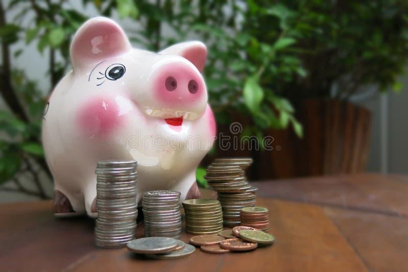 Розовая копилка с некоторыми монетками на коричневом деревянном столе стоковое фото rf