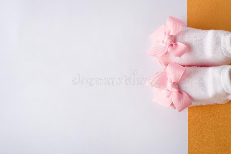 Розовые ботинки младенца на белой и желтой предпосылке носки маленькой девочки установьте текст скопируйте космос стоковые фотографии rf