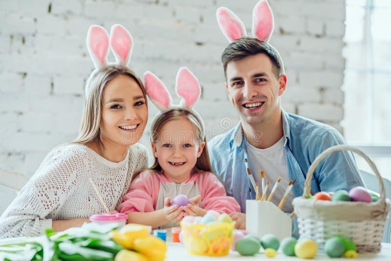 Розовые уши кролика добавляют праздничную атмосферу Счастливые пасхальные яйца краски семьи совместно Маленькая девочка держа пас стоковые изображения rf