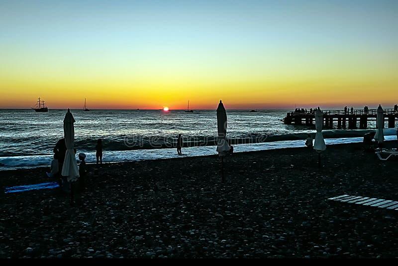 Романтичный вечер и волшебный заход солнца на пляже, силуэты людей стоковое изображение