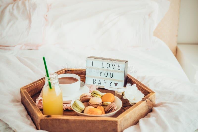 Романтичный завтрак в кровати с я тебя люблю текстом младенца на освещенной коробке Чашка кофе, сок, macaroons, цветок и подарочн стоковое изображение rf