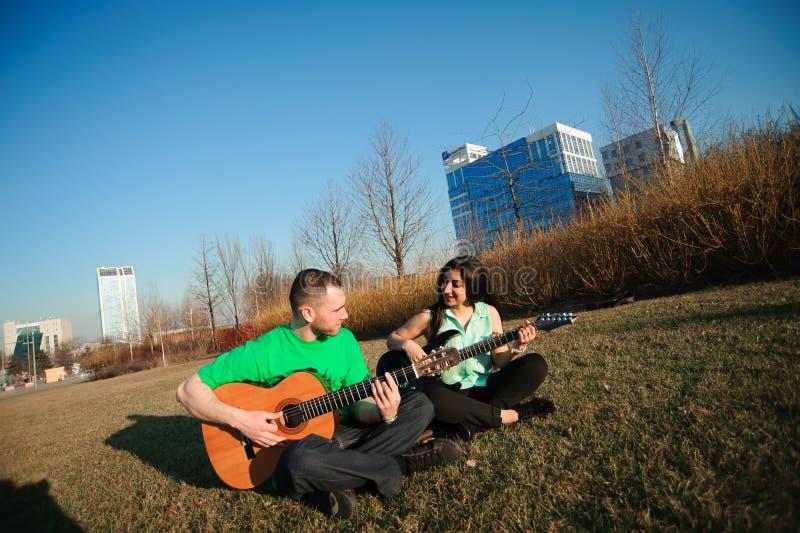 Романтичный молодой портрет пар играя гитару под голубым небом стоковые изображения rf