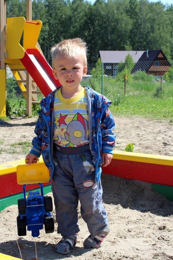 Ñ  Ñ€ÑƒÑ  Ñ 小男婴使用在沙盒的操场的五岁与玩具在夏天 免版税图库摄影