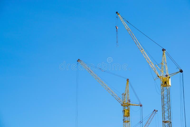 Żółci żurawie przy budową przeciw niebieskiemu niebu zdjęcia royalty free