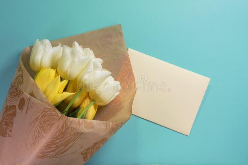 Żółci i biali tulipany z kopertą w opakunkowym papierze na lekkim turkusowym tle fotografia royalty free