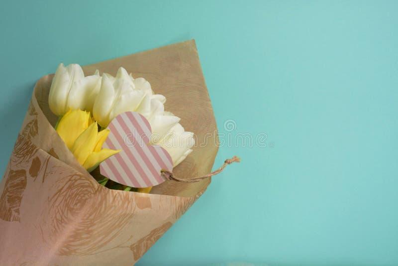 Żółci i biali tulipany z serce kartą w opakunkowym papierze na lekkim turkusowym tle obrazy stock