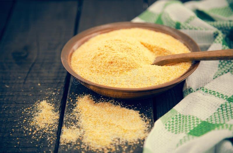 Żółta kukurydzana mąka w ceramicznym pucharze na nieociosanym drewnianym stole Składniki dla przygotowania Włoska tradycyjna pole obrazy royalty free