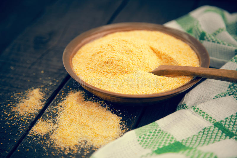 Żółta kukurydzana mąka w ceramicznym pucharze na nieociosanym drewnianym stole W fotografia royalty free