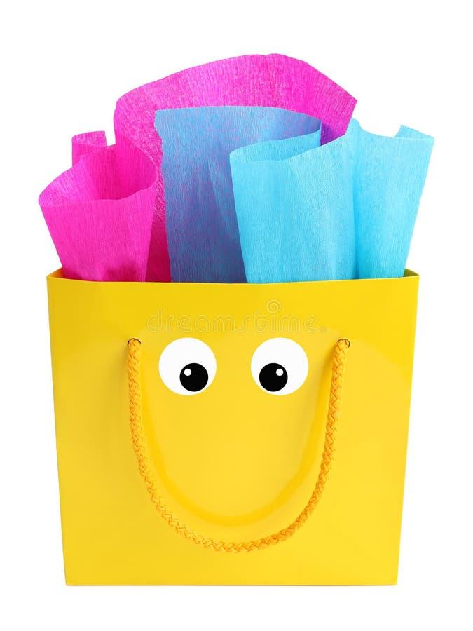 Żółta prezent torba z smiley twarzą na nim zdjęcie stock