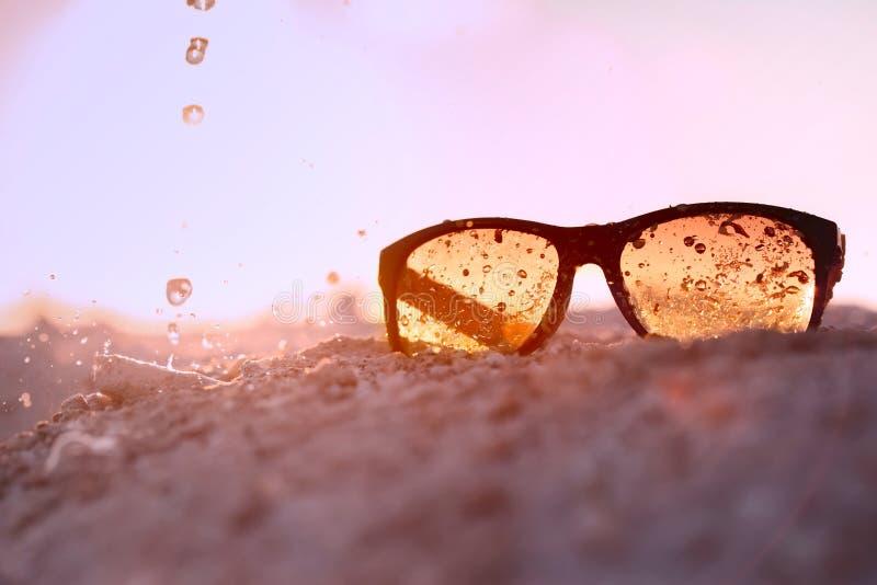 Żółtego sunglasseson piaskowata plaża z pluśnięciem zdjęcie royalty free