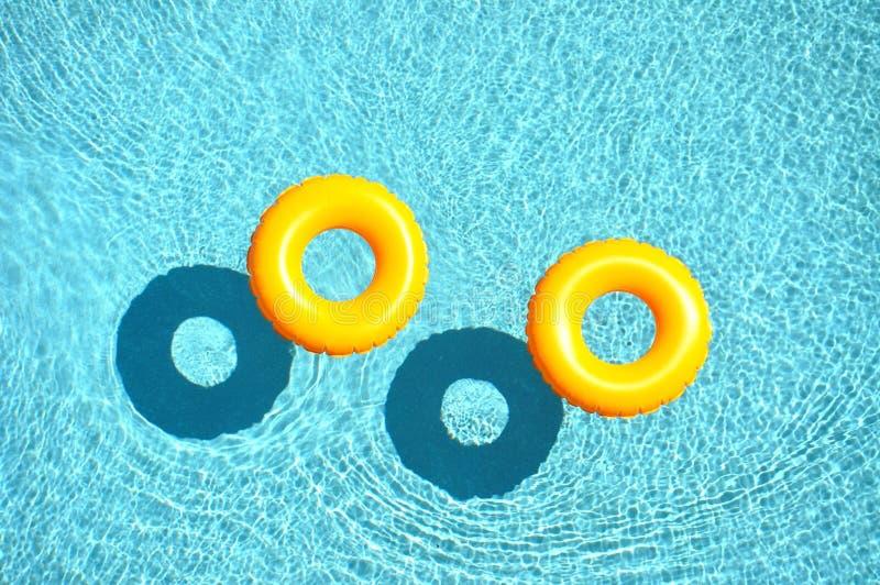 Żółty basenu pławik, basenu pierścionek w chłodno błękitnym odświeżającym błękitnym basenie fotografia royalty free