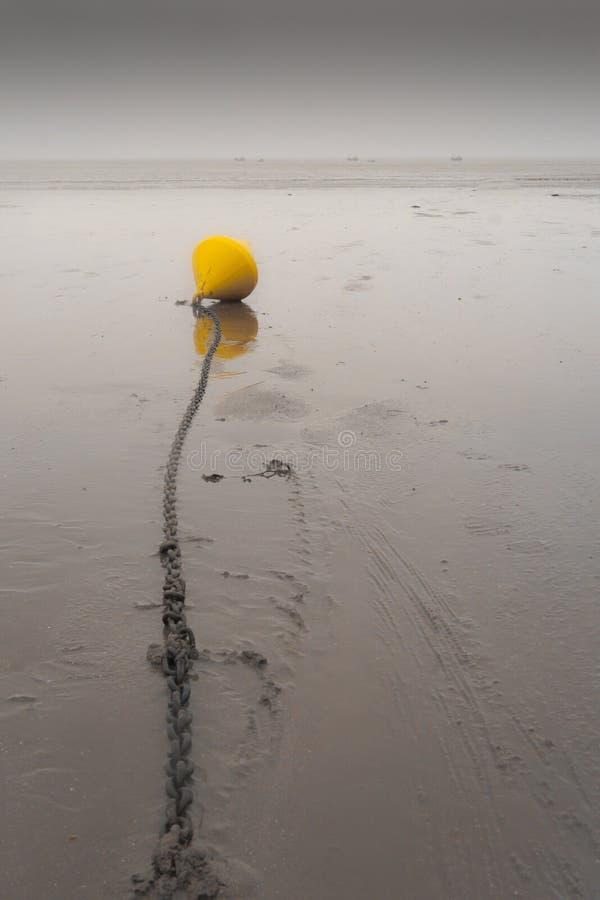 Żółty bouy na łańcuchu na plaży zdjęcie stock