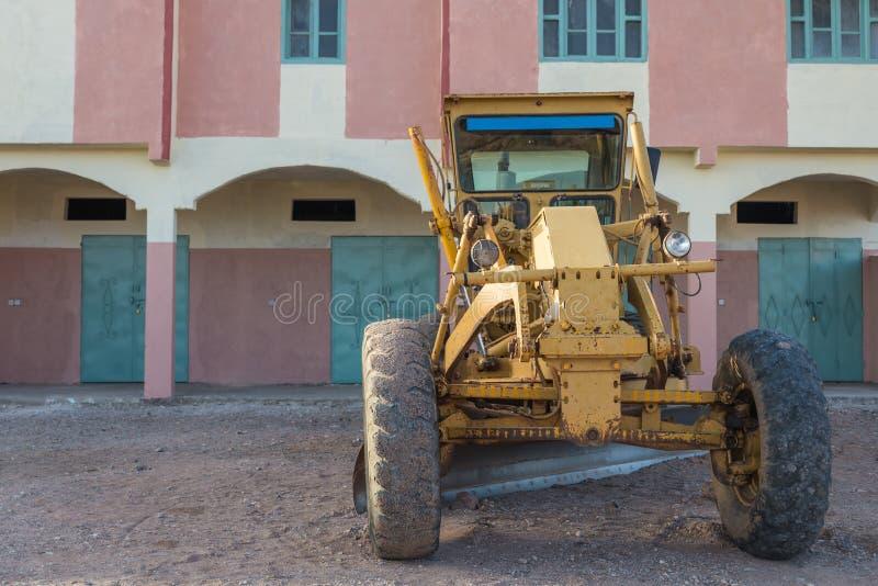 Żółty buldożeru park przed kolorowym budynkiem fotografia stock