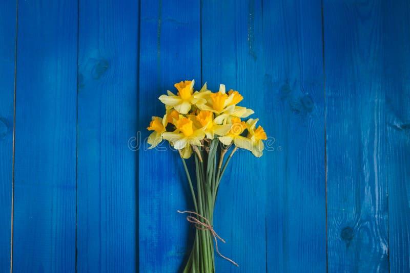 Żółty daffodils bukiet na błękitnym drewnianym tle, Easter karta zdjęcia stock