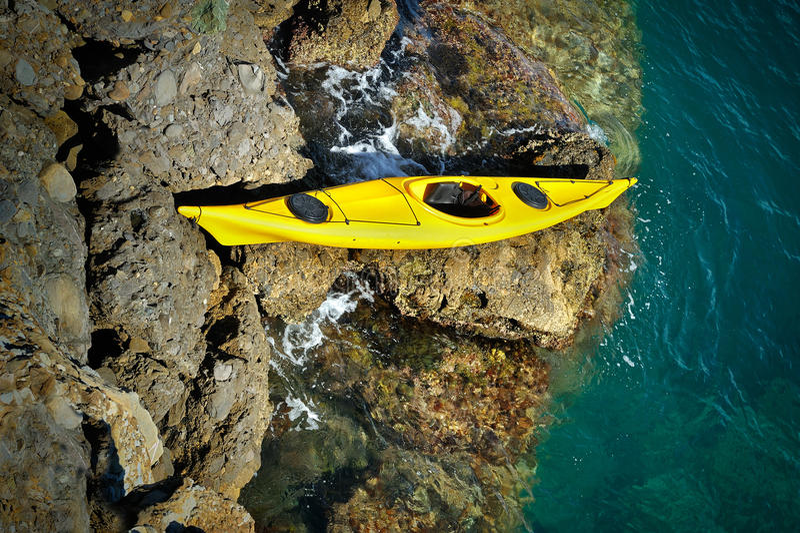 Żółty denny kajak wyrzucać na brzeg na skalistych gwałtownych fotografia stock